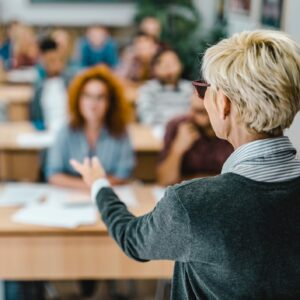 Rear view of mature teacher giving a lecture in a classroom.